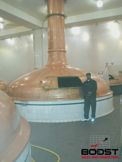 Paul Gage at Coors Brewery next to the large beer kettle